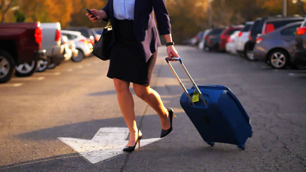 Businesswoman pulling suitcase. stock photo
