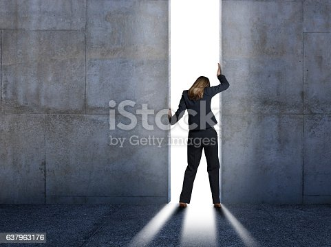 A rear view of a businesswoman as she struggles to open up doors to the outside world. A strong light filters through from outside casting a strong shadow across the floor.
