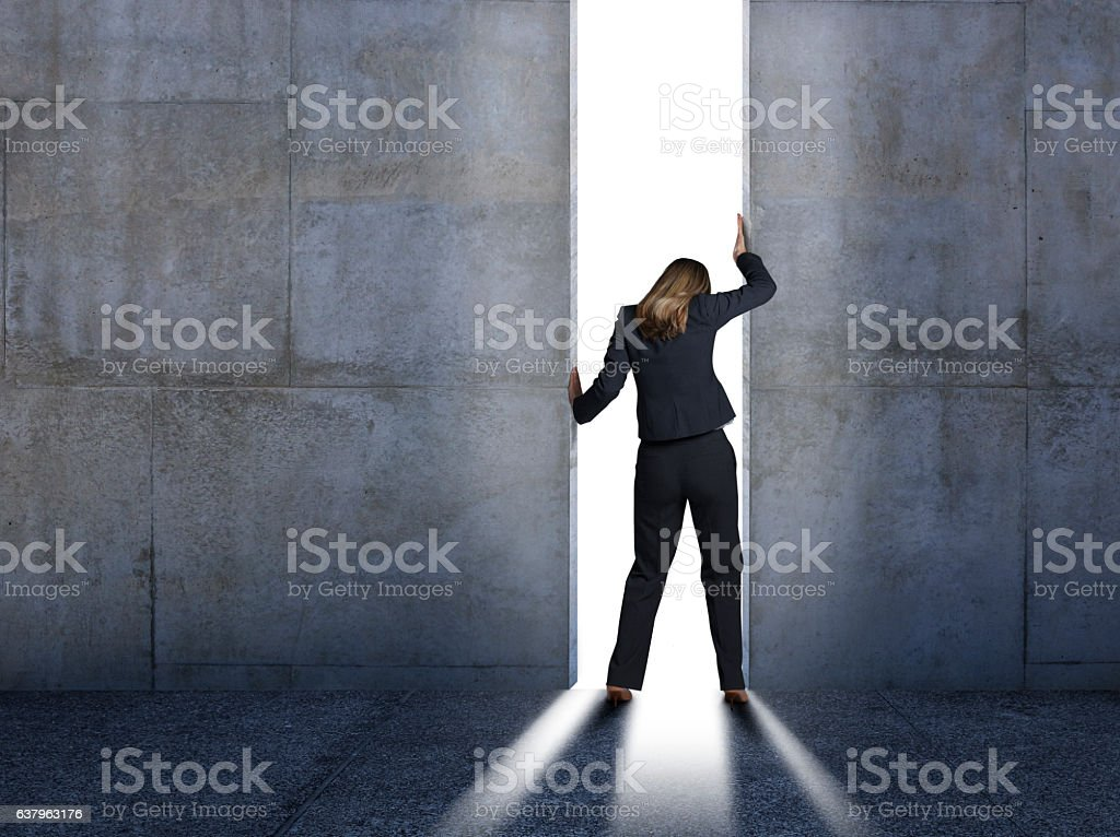 Businesswoman Pushing Open Concrete Walls stock photo