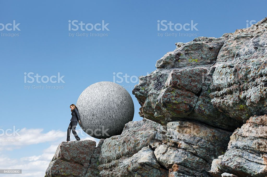 Businesswoman Pushing Sphere Up Rocky Cliff stock photo