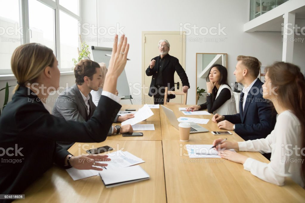 Businesswoman raising hand asking senior coach questions at team meeting foto stock royalty-free