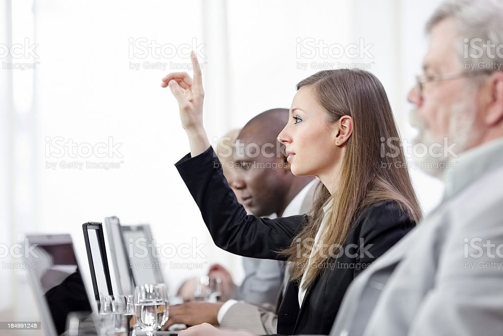 Businesswoman raising hand during business meeting royalty-free stock photo