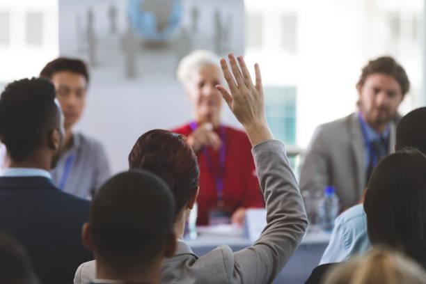 Businesswoman raising hand in a business seminar stock photo