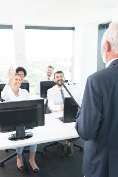 Businesswoman raising hand to ask question at team training stock photo