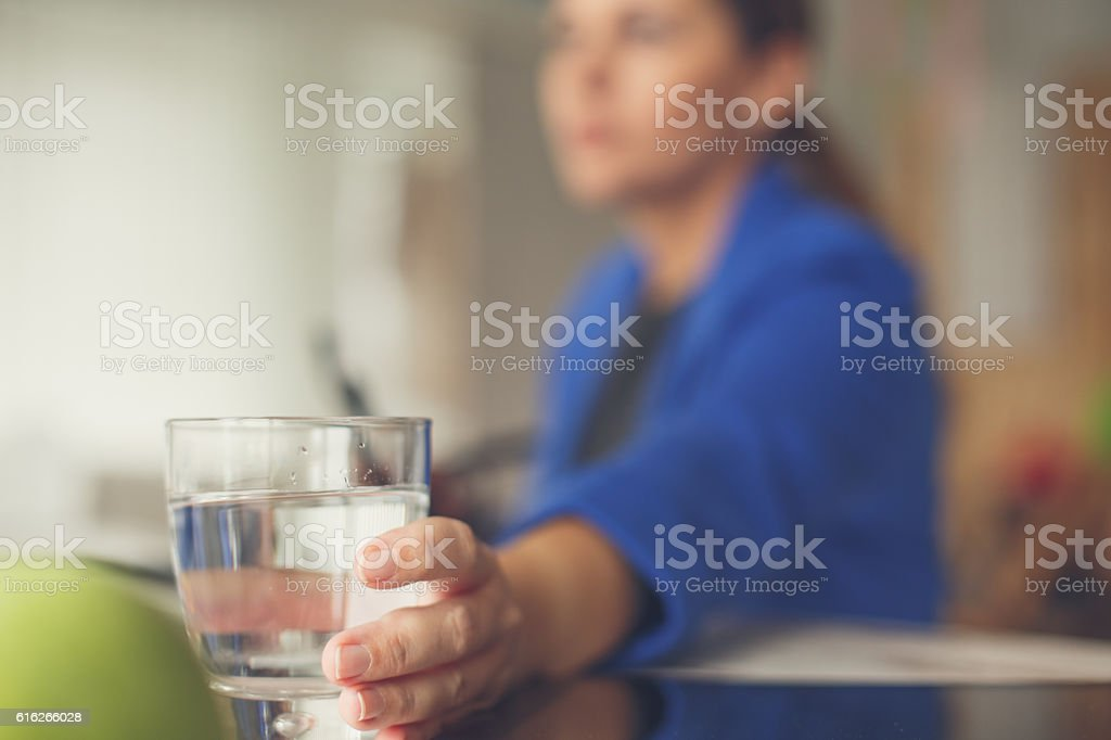 Businesswoman reaching for glass of water stock photo
