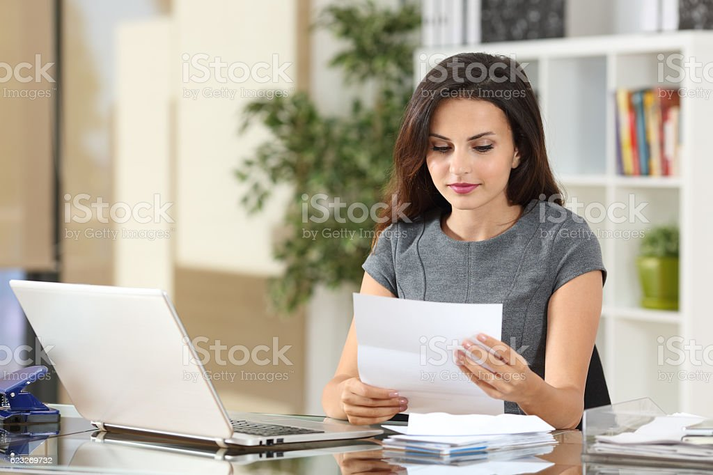 Businesswoman reading a letter at office stock photo