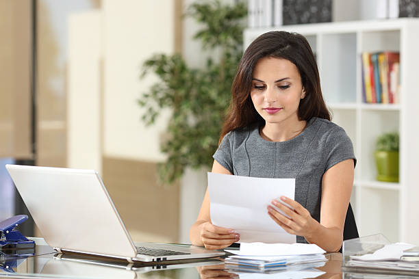 businesswoman reading a letter at office - mail stock photos and pictures