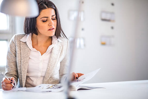 Businesswoman reading brochure while taking notes in office – Foto