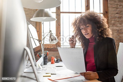 Concentrated mid adult businesswoman reading document. Female professional is doing paperwork at computer desk. She is wearing smart casuals in creative office.