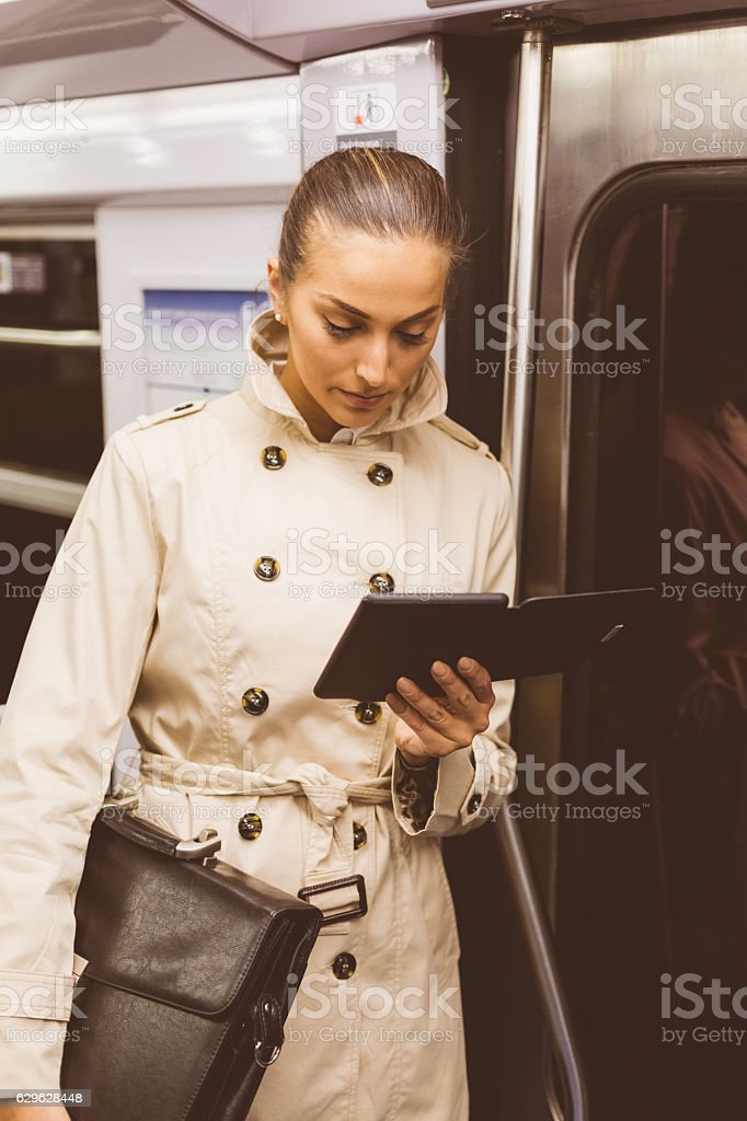Businesswoman reading e-book in the subway stock photo