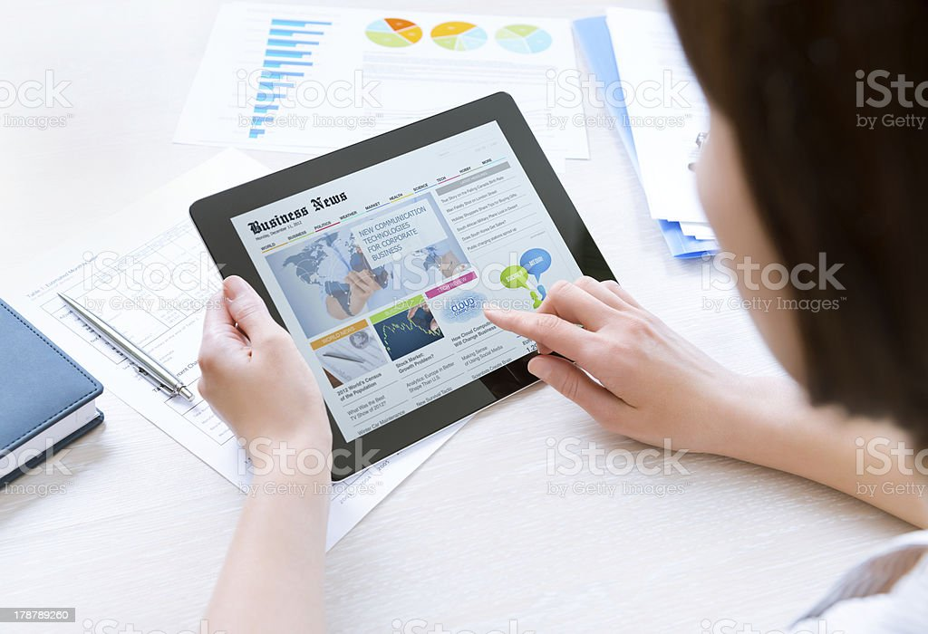 Businesswoman reading latest news on tablet stock photo