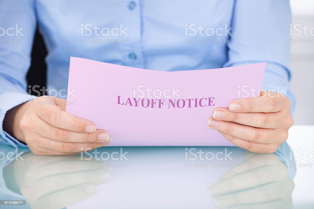 Businesswoman Reading Layoff Notice stock photo