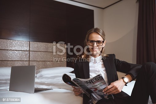istock businesswoman reading magazine in hotel 913759364
