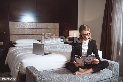 istock businesswoman reading magazine in hotel 913760470