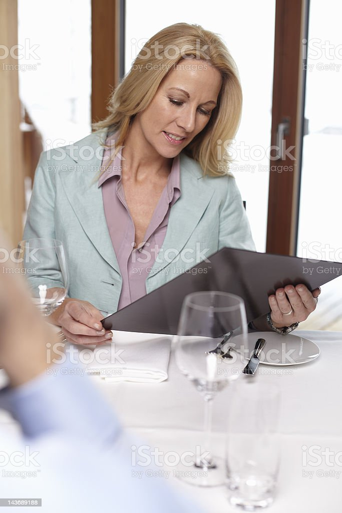 Businesswoman reading menu in cafe royalty-free stock photo