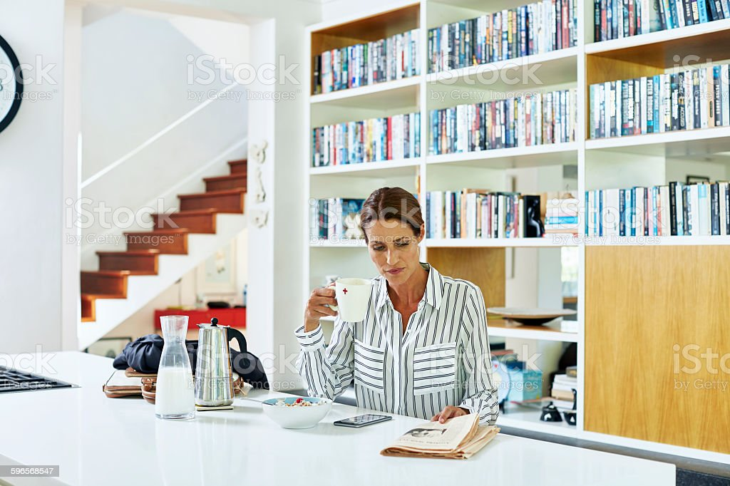 Businesswoman reading newspaper at home stock photo