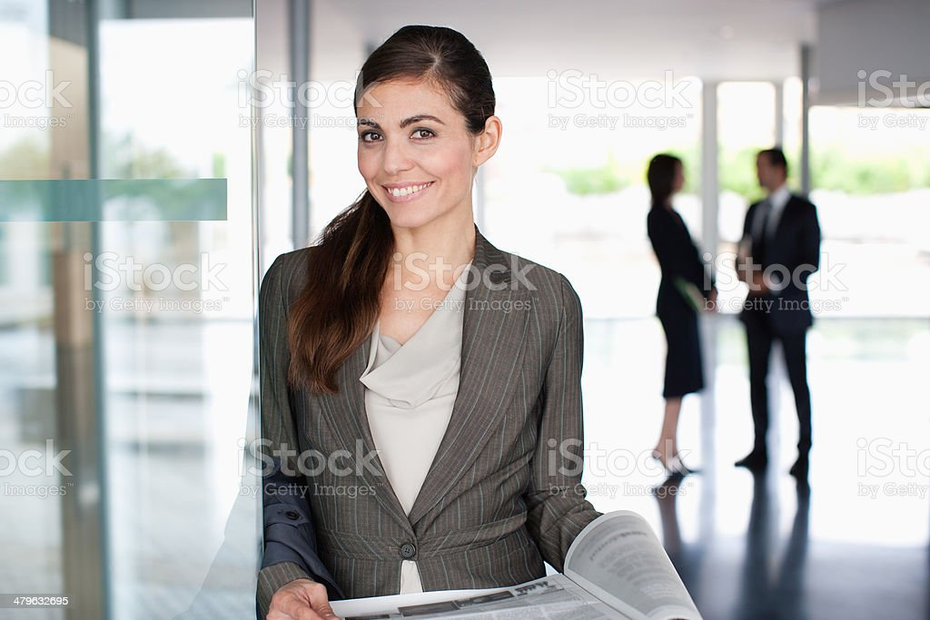 Businesswoman reading newspaper in lobby stock photo