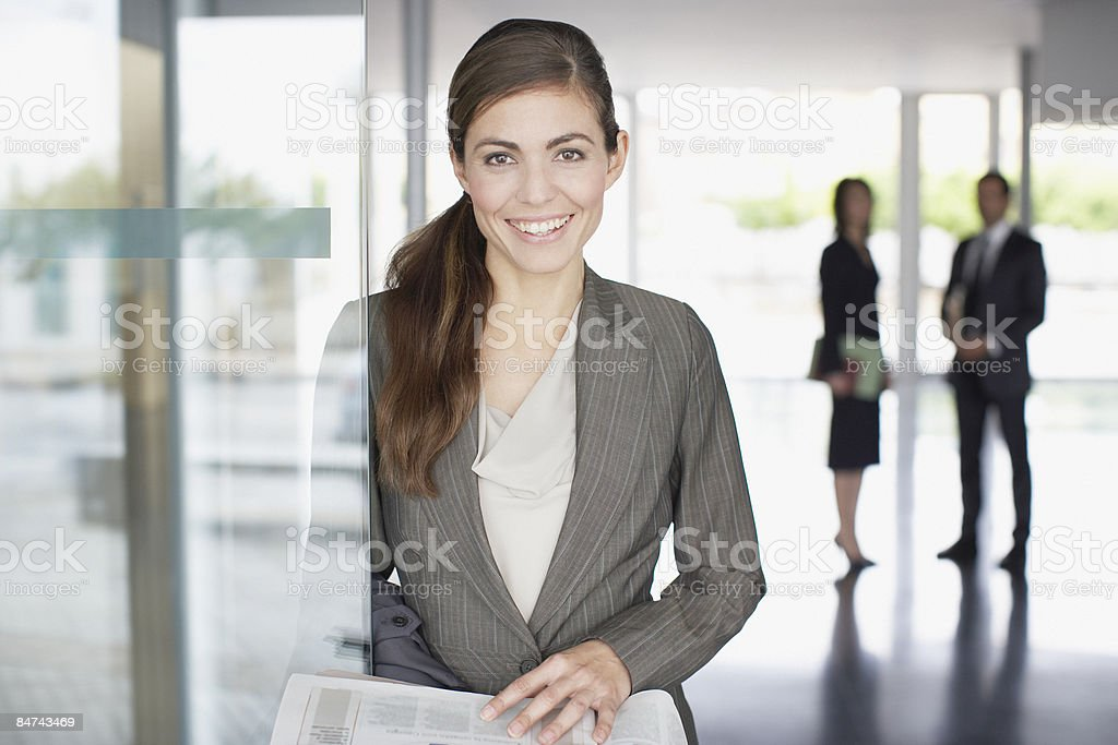 Businesswoman reading newspaper in office lobby royalty-free stock photo