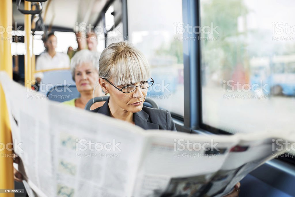 Businesswoman reading newspapers in bus. stock photo