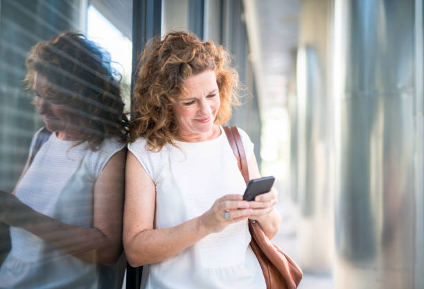 businesswoman reading text message on smart phone - older woman phone stock photos and pictures