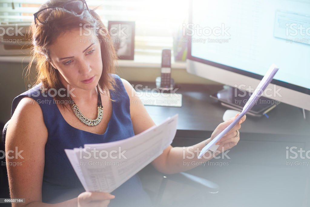 Businesswoman reads through client paperwork stock photo