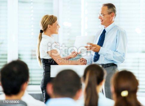 Blonde businesswoman receiving a certificate after a successful training seminar.