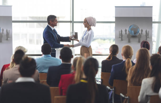 Businesswoman receiving award from businessman in a business seminar stock photo