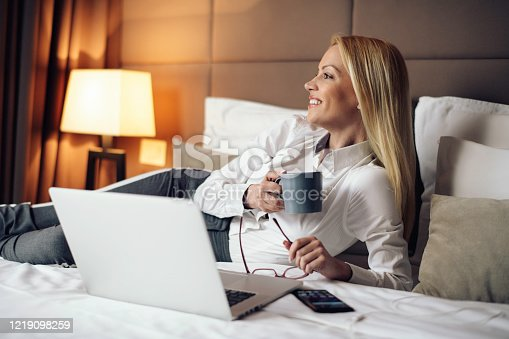 947825822 istock photo Businesswoman relax after work in hotel room. 1219098259