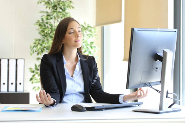 businesswoman relaxing doing yoga at office - mindfulness stock photos and pictures