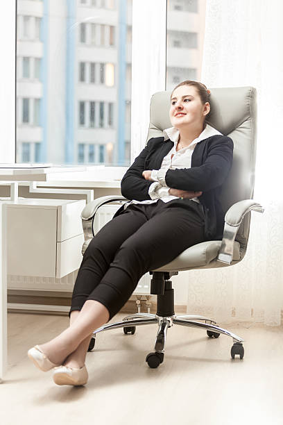 businesswoman relaxing in leather chair at office stock photo