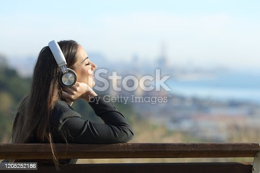 Businesswoman relaxing listening to music wearing headphones sitting on a bench outdoors