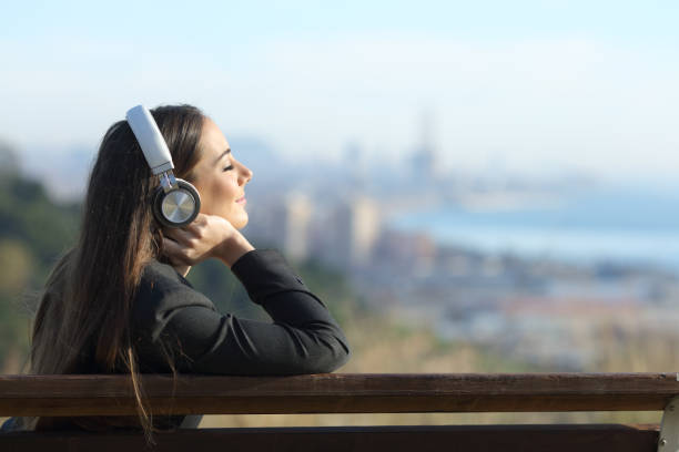 Businesswoman relaxing listening to music outdoors stock photo