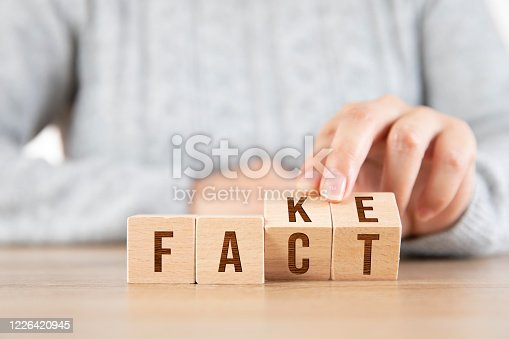 Female hand replacing wooden Cube blocks from Fake to Fact word