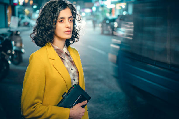 Businesswoman returns from office and waits for a bus on a busy road at night. stock photo