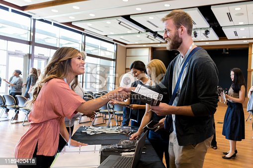 Caucasian businessman greets a female associate during a conference. The woman is working at the conference registration tablet.