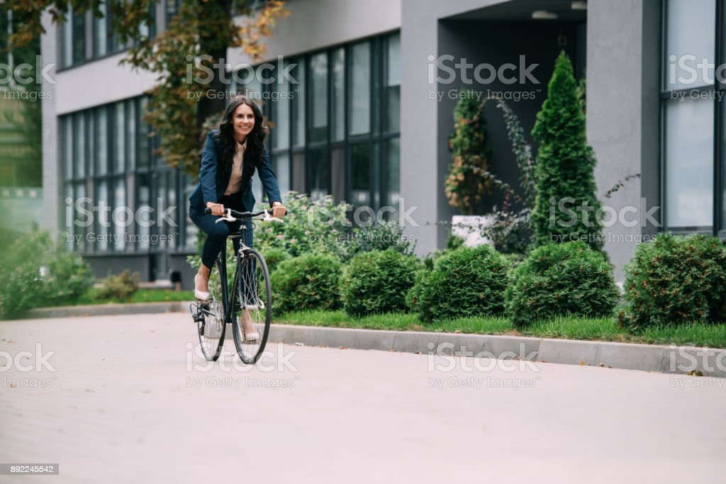 businesswoman riding bicycle stock photo