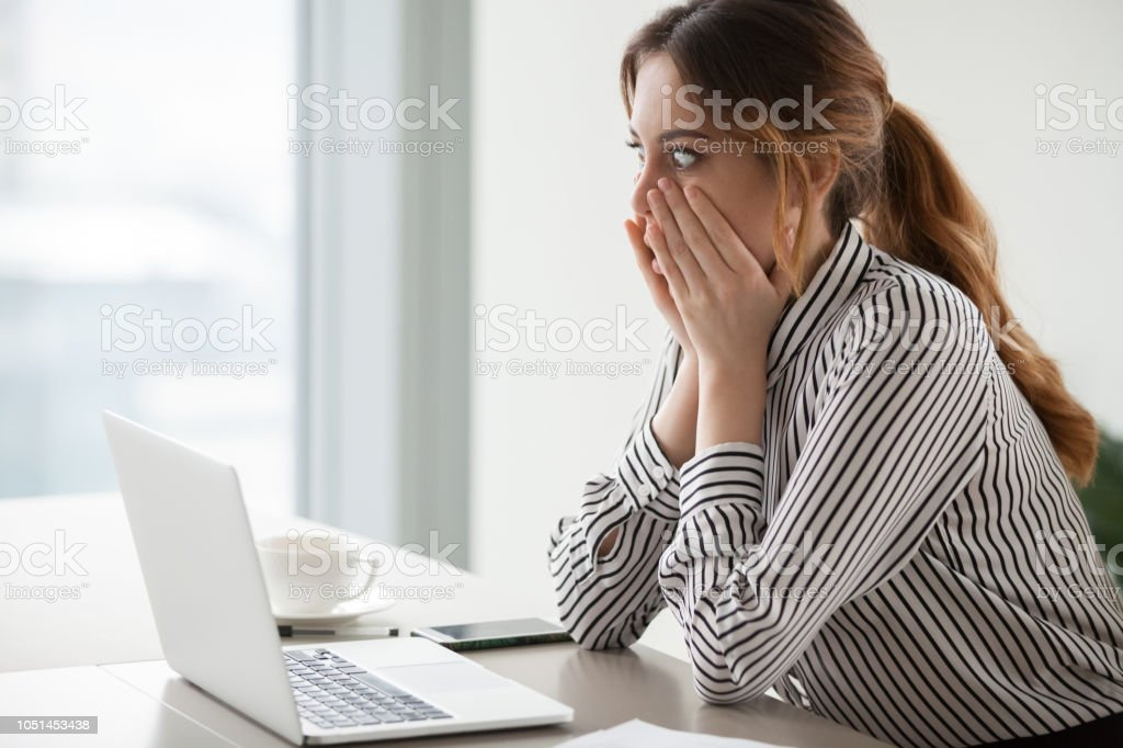 Shocked woman worker looking at laptop screen surprised with bad or...