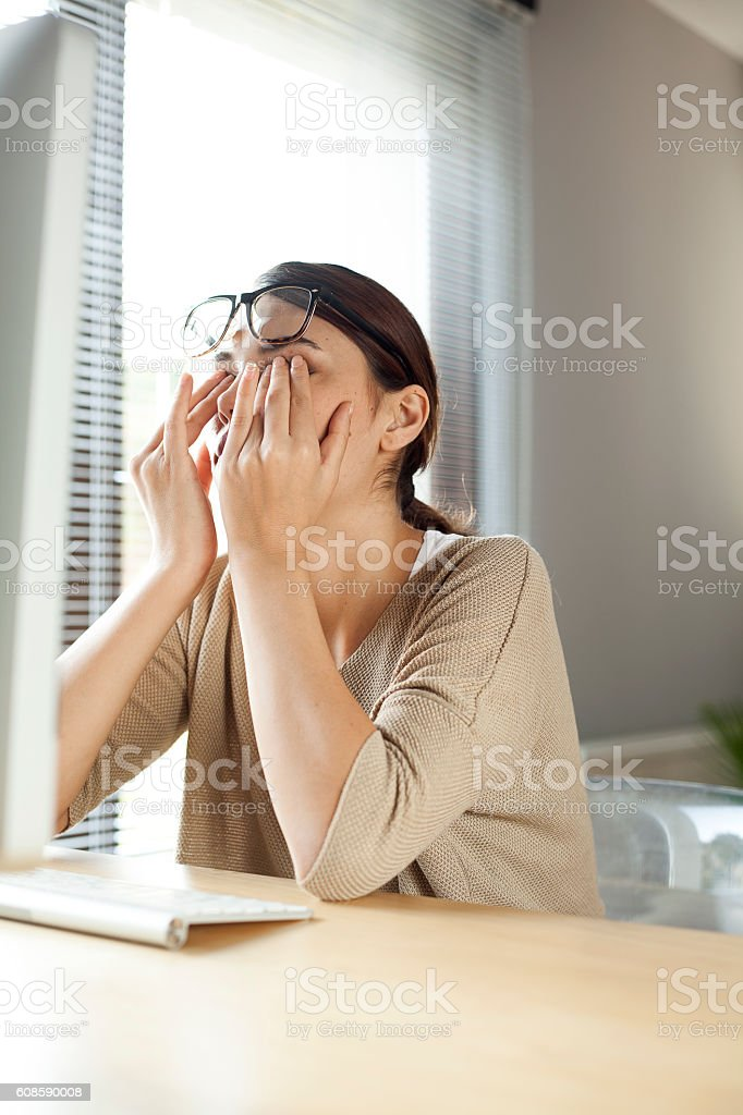 Businesswoman rubbing her tired eyes stock photo