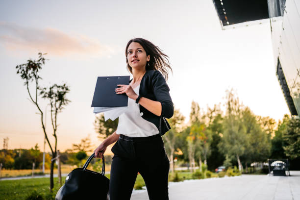 Businesswoman running late in office stock photo