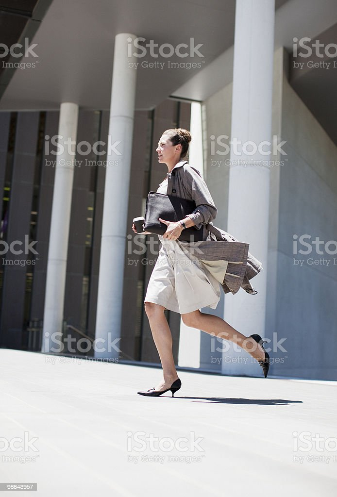 Businesswoman running outdoors stock photo