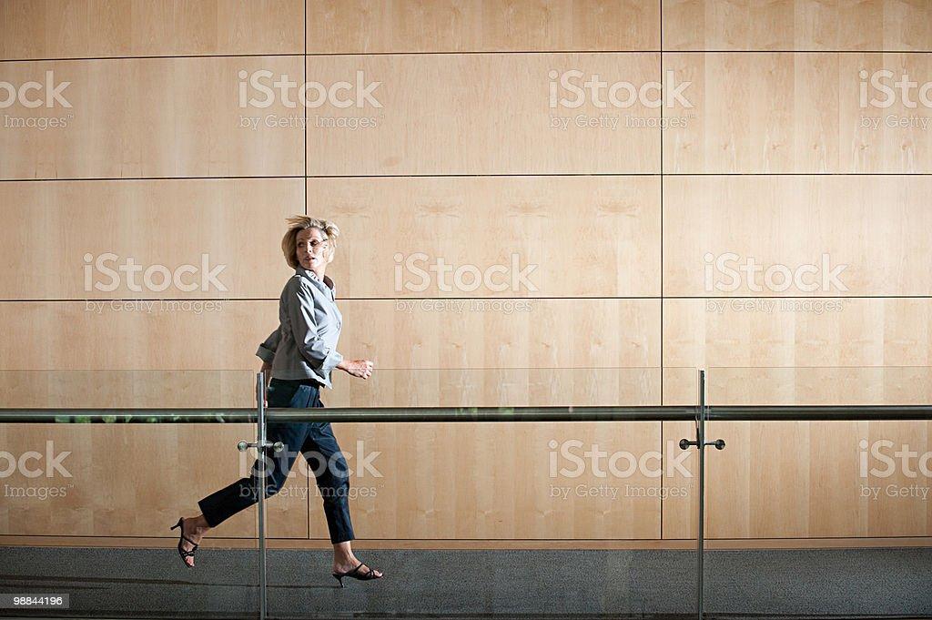 Mulher de Negócios em execução através de corredor foto de stock royalty-free