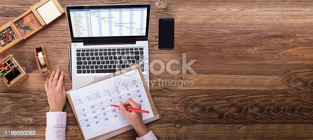 An Overhead View Of Businesswoman Marking Date On Calendar With Gantt Chart On Laptop Screen