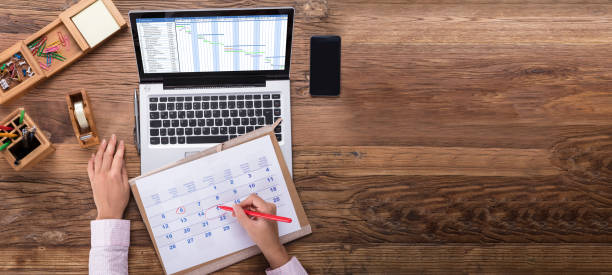 Businesswoman Scheduling The Plan Using Calendar And Laptop An Overhead View Of Businesswoman Marking Date On Calendar With Gantt Chart On Laptop Screen business stock pictures, royalty-free photos & images
