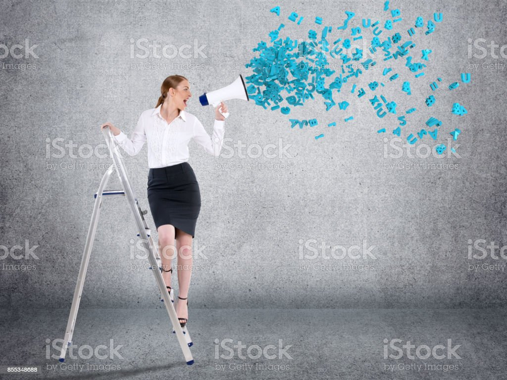 Businesswoman screaming into megaphone stock photo