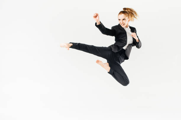 businesswoman screaming, jumping and performing kick in suit isolated on white stock photo