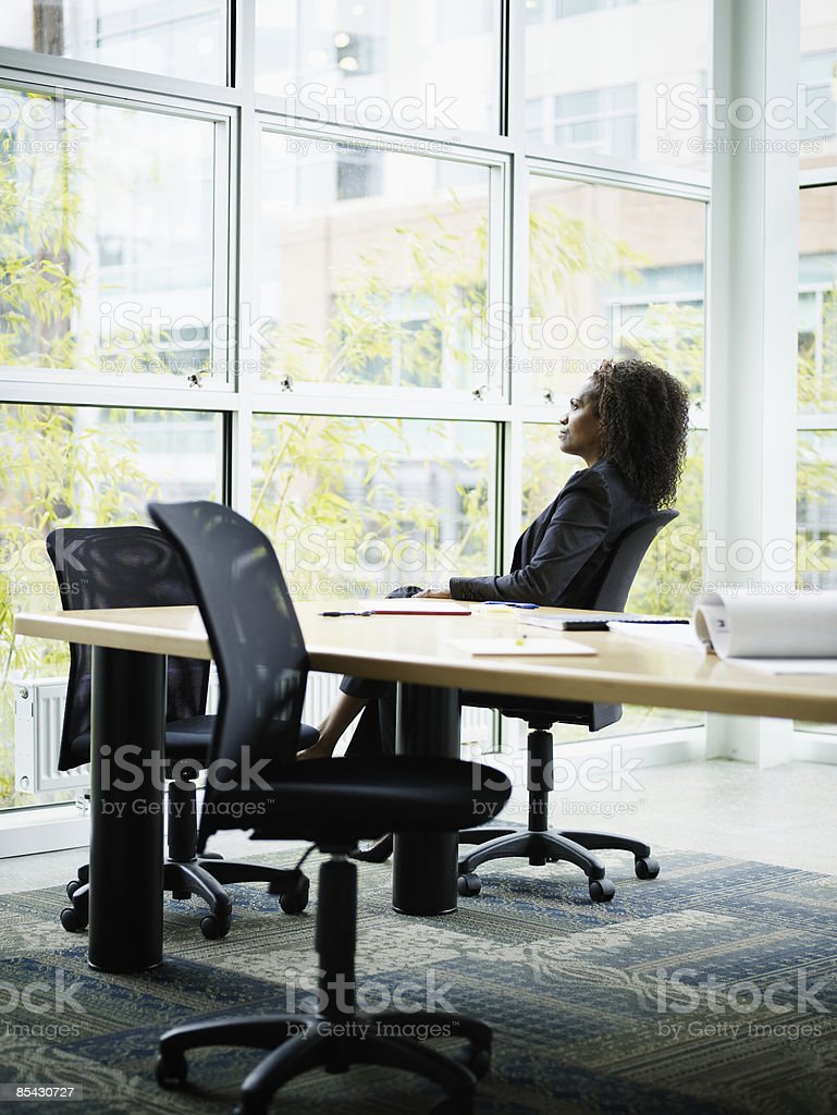 Businesswoman seated at conference table royalty-free stock photo