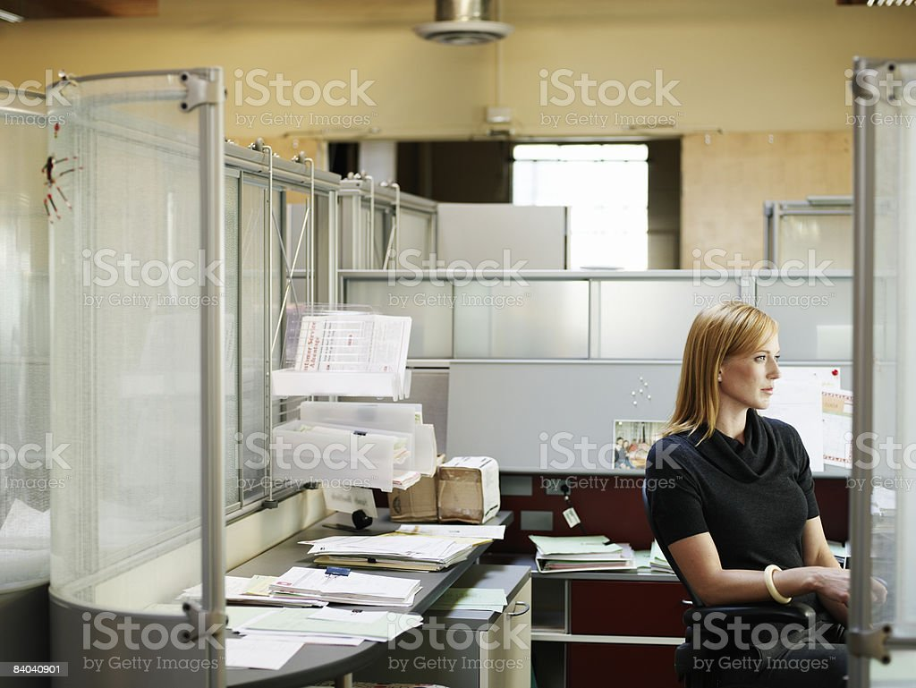 Businesswoman seated in office cubicle photo libre de droits