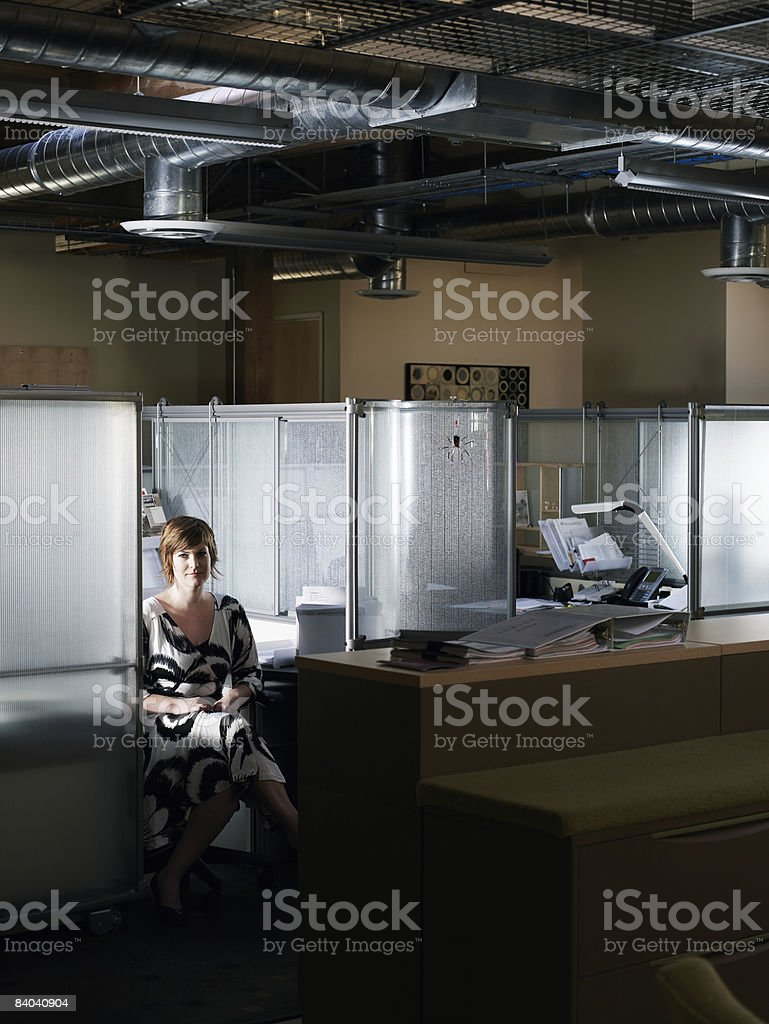 Businesswoman seated in office cubicle royalty-free stock photo