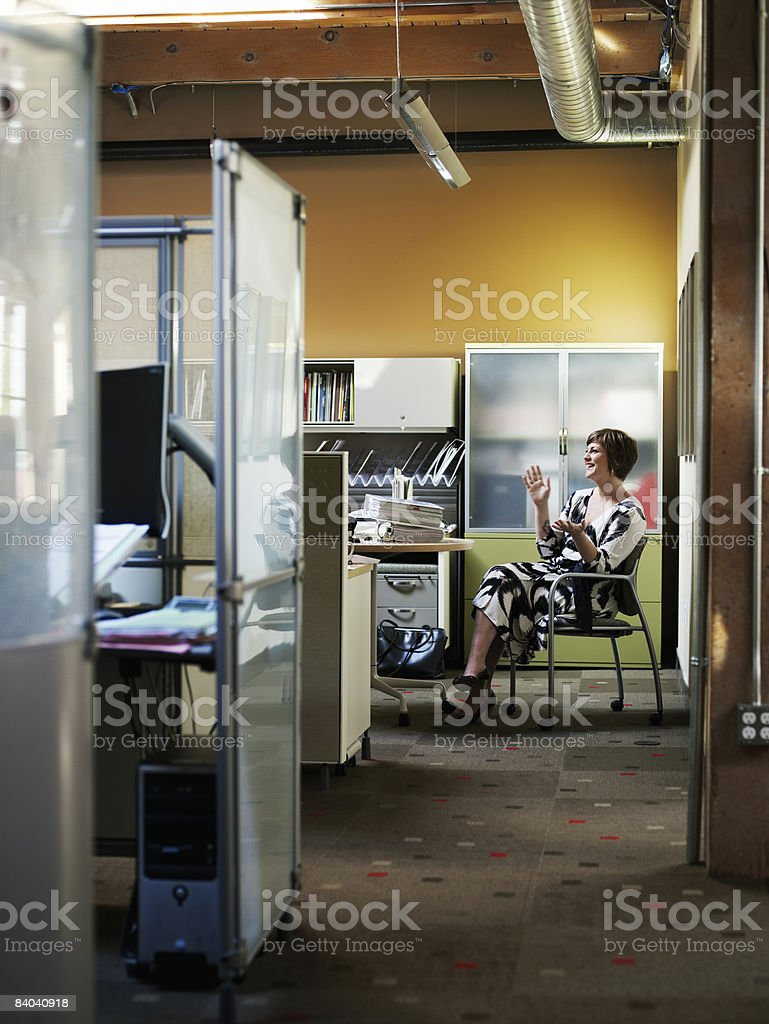 Businesswoman seated in office, laughing foto stock royalty-free