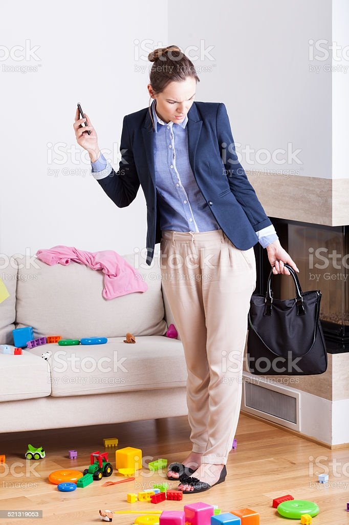 Businesswoman seeing mess in house stock photo